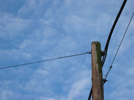 The wire as it connects to the telephone pole on this side of the canal